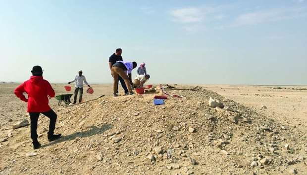 Researchers excavating a pre-Islamic burial mound in the Asaila area west of Umm Bab in order to rec