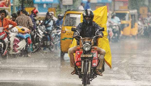 A motorist rides on a road during heavy rain in Chennai yesterday.