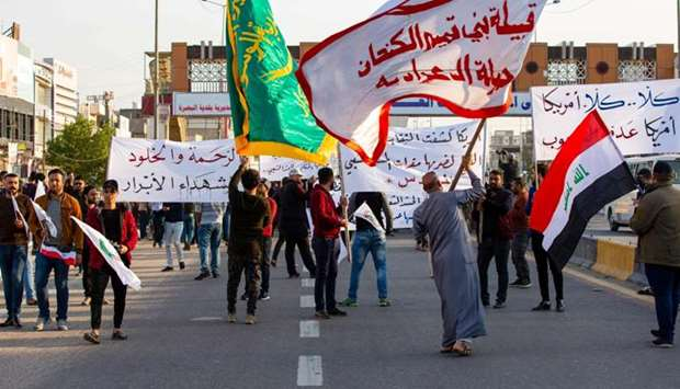 Iraqis wave Hashed Al-shaabi armed network flags in the southern city of Basra, during a demonstrati