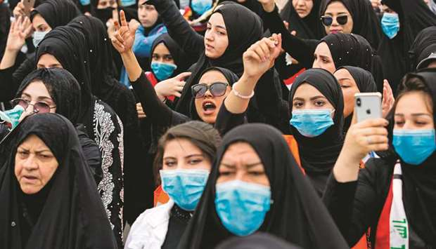 An Iraqi woman raises her fist as she takes part in an anti-government march in the centre of the so