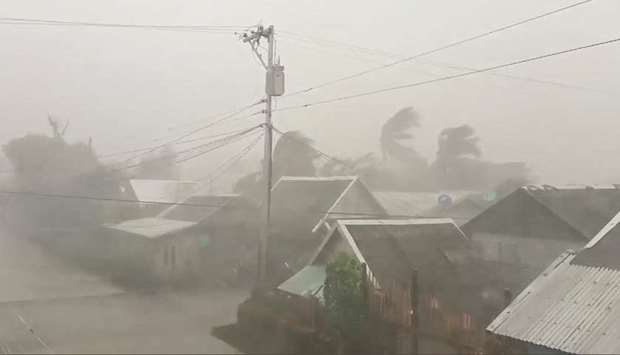 Trees sway near buildings as Typhoon Kammuri makes landfall in Gamay, northern Samar, yesterday, in