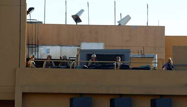 US soldiers take their position on the roof of the US Embassy during a protest to condemn air strike