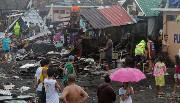 Residents stand among their damaged houses after Typhoon Kammuri hit Legazpi City, Albay, Philippine
