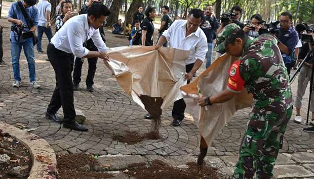 Police cover a blood spilled with soil at the blast site in Jakarta yesterday.