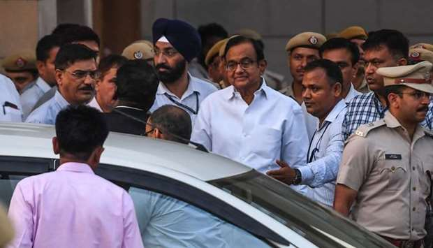 India's former finance minister Palaniappan Chidambaram (C in white shirt with glasses) leaves a cou