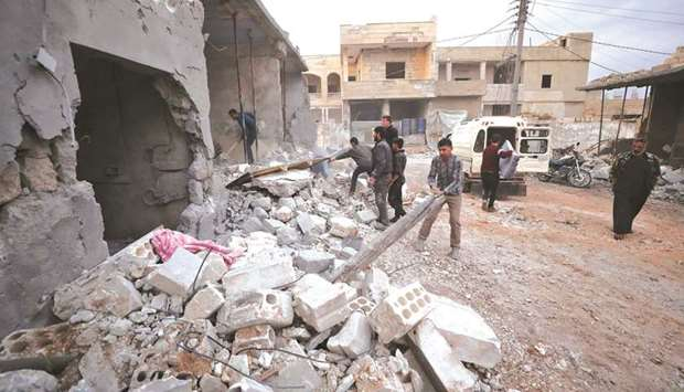 Residents salvage items from the rubble of a building following a reported air strike by pro-regime