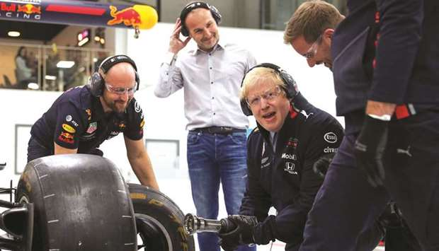 Prime Minister Boris Johnson changes a wheel of a Formula One (F1) race car during a Conservative Pa