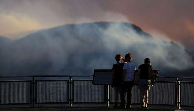 People watch as smoke from the Green Wattle Creek fire is seen from Echo Point lookout in Katoomba,