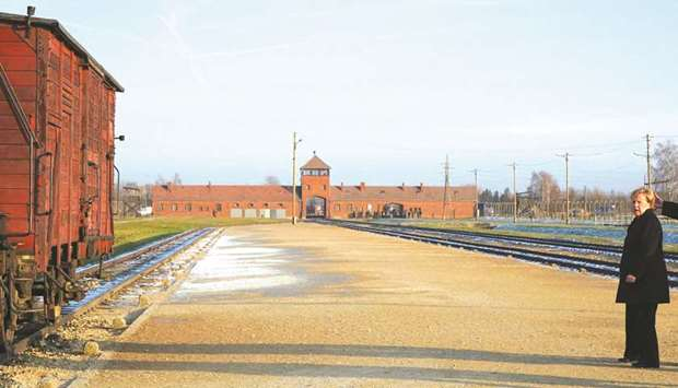 Merkel walks in front of the main railway entrance to Birkenau during her visit to the former German