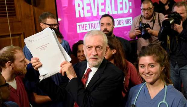 Britain's opposition Labour Party leader Jeremy Corbyn holds up documents as he poses for a picture