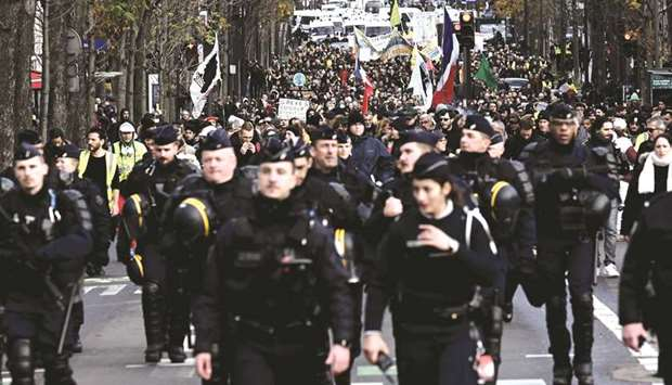 Anti-riot police personnel walk ahead of members of the 'yellow vest' movement demonstrating in Pari