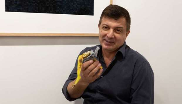 David Datuna shows the remains of the artwork 'Comedian' by the artist Maurizio Cattelan at Perrotin