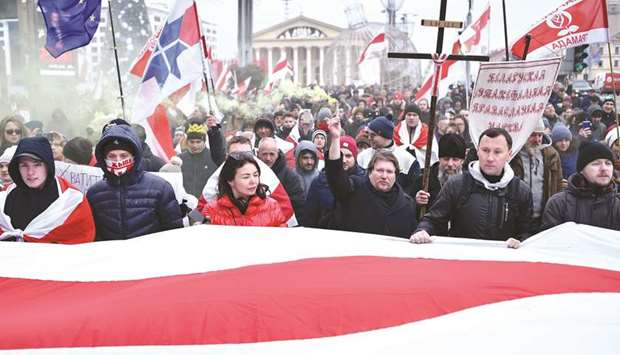People carry a giant Belarusian white-red-white flag and anti-integration banners during a rally in
