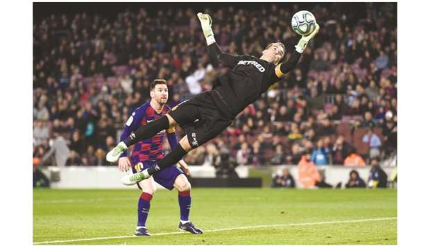 Barcelona's Lionel Messi (left) looks at Real Mallorca goalkeeper Manolo Reina attempt a save during