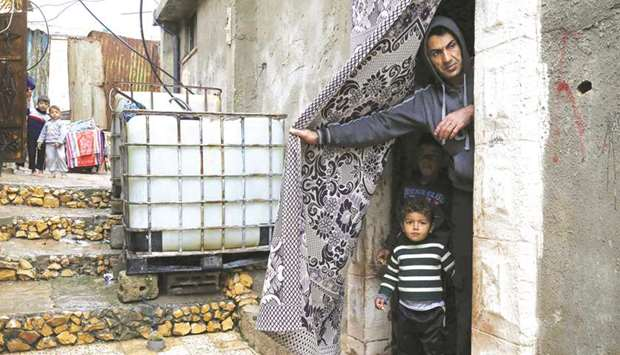 A Palestinian man stands with a child at the door of their home near the site of troops' overnight a