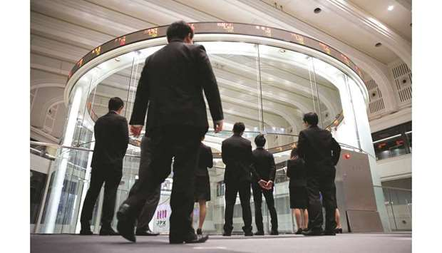Visitors watch share prices at the Tokyo Stock Exchange in Japan. The Nikkei 225 closed up 0.3% to 2