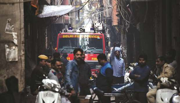 A Delhi Fire Service truck is seen along a street near the site where a fire broke out in Anaj Mandi
