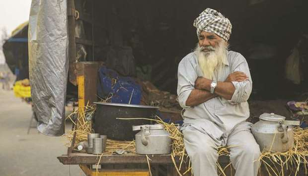 A farmer sits in a tractor trolley during a protest against the newly-passed farm bills at Singhu bo