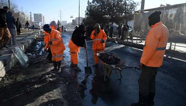 Municipal workers clean and remove debris along a street after multiple rockets were fired in the Af
