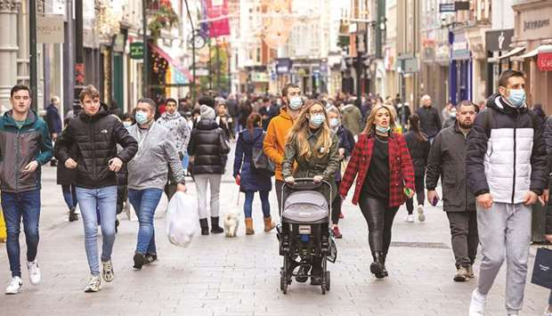 Pedestrians, some wearing face masks or coverings due to the Covid-19 pandemic, walk along a busy sh