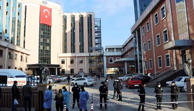 Police and security personnel stand guard outside the private Sanko University Hospital where a fire