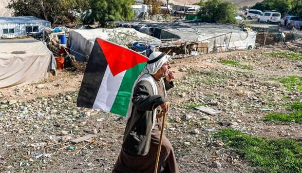A Bedouin man walks with a Palestinian flag in the village of Khan al-Ahmar