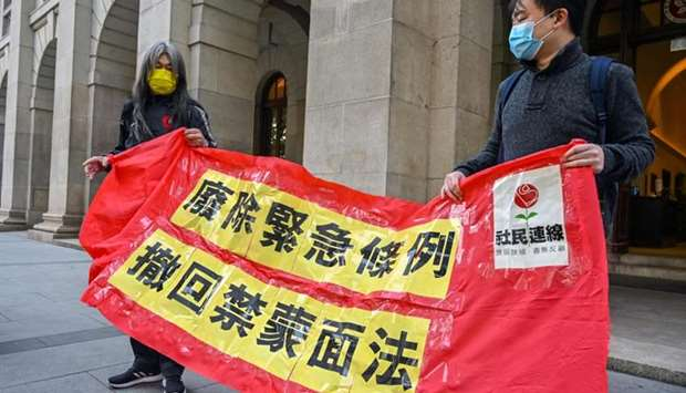 """Leung Kwok-hung also known as """"Long Hair"""" (L) holds a banner that reads """"Abolish the Emergency Regul"""