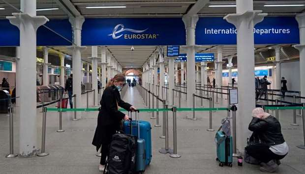 Travellers wearing protective face coverings to combat the spread of the coronavirus prepare to depa
