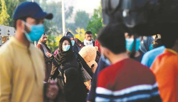 Passengers wearing face masks as a preventive measure against the Covid-19 coronavirus arrive at the