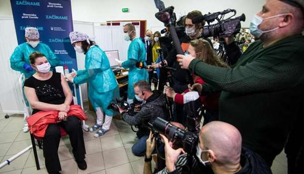 A woman sits on a chair in front of medias as she receives a vaccination against the novel coronavir