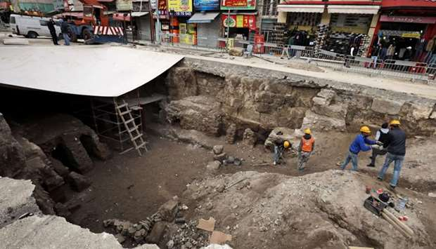 Archaeologists and workers excavate at a Roman archaeological site discovered during works to instal
