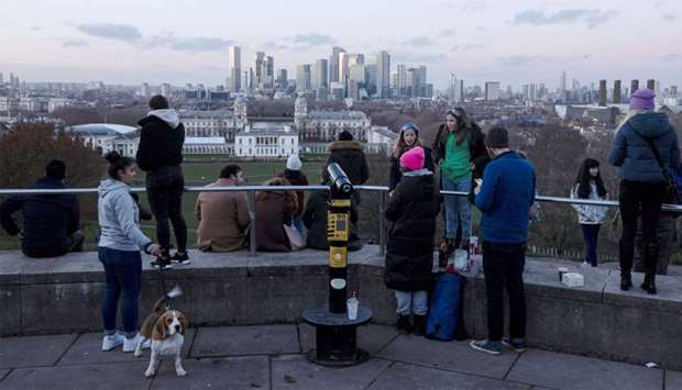 People look towards Canary Wharf from Greenwich Park in London, Britain