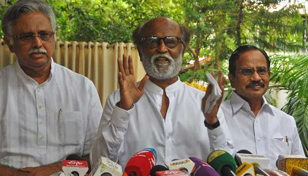 Indian actor Rajinikanth (C) addresses the media representatives in front of his residence in Chenna