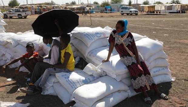 Ethiopian refugees sit on bags of food aid at the Village 8 refugees transit camp, which houses Ethi