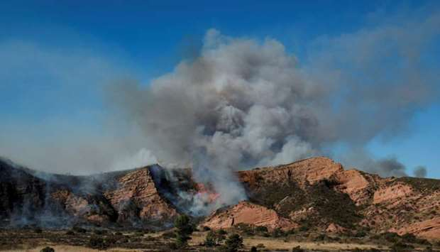 Smoke rises from the Bond Fire as evacuation orders are issued for nearby residents in Orange County