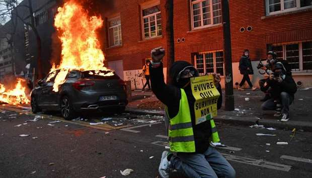 """A """"Yellow Vest"""" (Gilet Jaune) anti-government protestor kneels raising his fist as he poses with a s"""