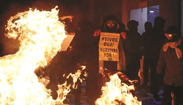 A demonstrator holds a sign reading 'Living, yes! Surviving, no!' during a protest in Paris.