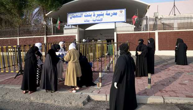 Kuwaiti women gather at the entrance of a polling station during parliamentary elections in Jahra Ci