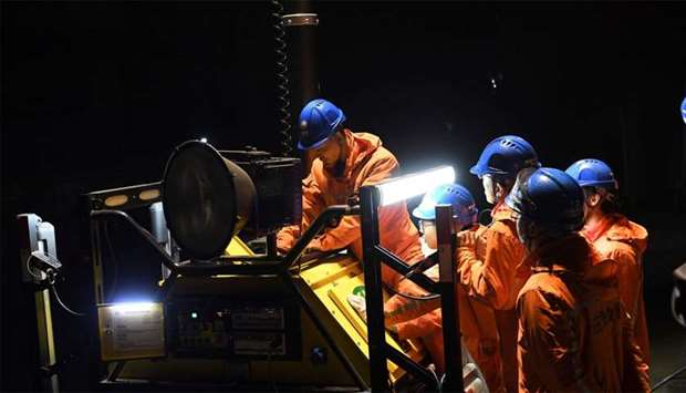 Rescuers adjust an emergency generator at the Diaoshuidong coal mine in southwestern China's Chongqi