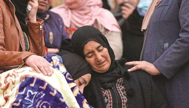 The mother and sister of Palestinian teenager Ali Abu Aliya mourn during his funeral in the village