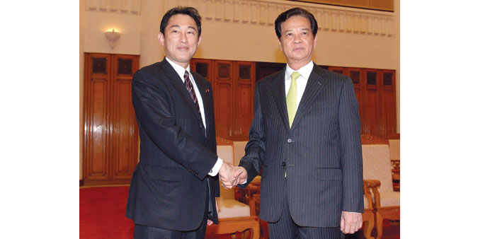 Japan's Foreign Minister Kishida Fumio, left, shaking hands with Vietnamese Prime Minister Nguyen Ta