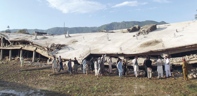Pakistani residents gather beside a collapsed building following an earthquake in the Koga area in B