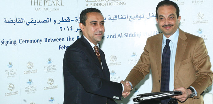 Ehab Kamel and Aly Delawar exchange documents at the agreement signing between Pearl-Qatar and Al Si