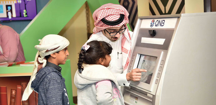 Children in front of the model of an ATM at the QNB booth (supplied picture).