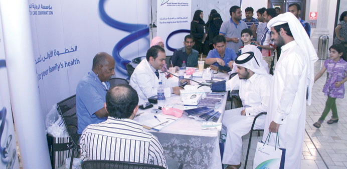 Residents are seen at the PHCC booth set up for the Ramadan health awareness campaign.