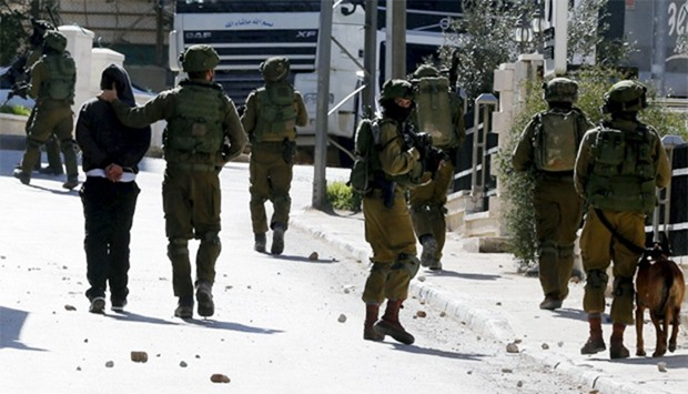 Israeli soldiers arrest a stone-throwing Palestinian during clashes in al-Amari refugee camp