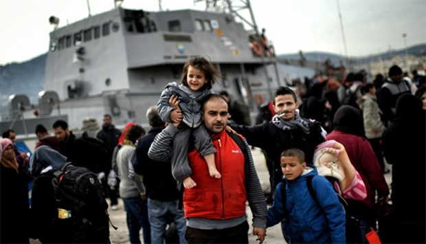 Refugees and migrants disembark from a Greek coast guard vessel in Mytilene