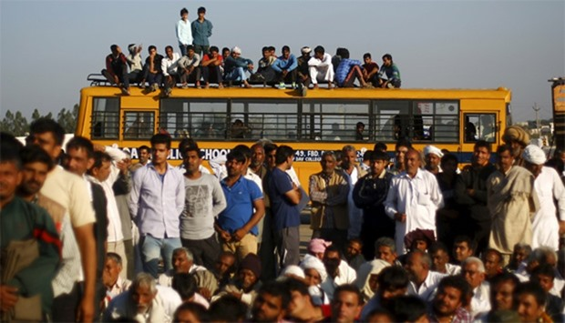 Demonstrators from the Jat community sit on top of a school bus