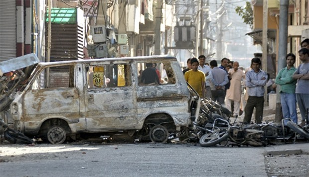 People stand behind damaged motorcycles and a van that were set alight by protesters in Haryana