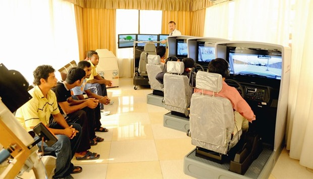 Students practice on simulators at a driving school